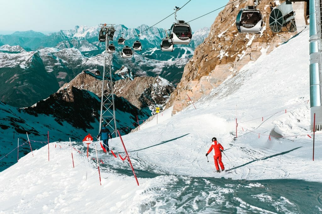 Person in red overall skiing under ski lift