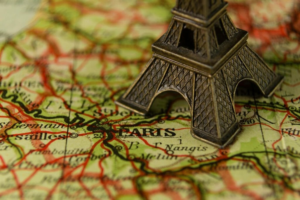 Toy Eiffel Tower over Paris on a map