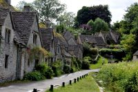 picturesque stone houses along narrow street in the cotswolds, England
