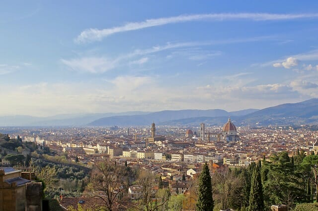View of the great city of Florence on a clear day with the roofs peaking through the green trees