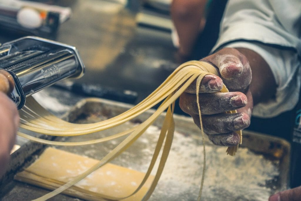 Chefs hands roll cutting fresh linguini with flour dusting his hands