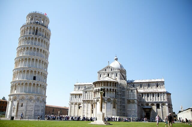 The Leaning Tower of Pisa next to a cathedral with hoards of tourists waiting to snap pictures