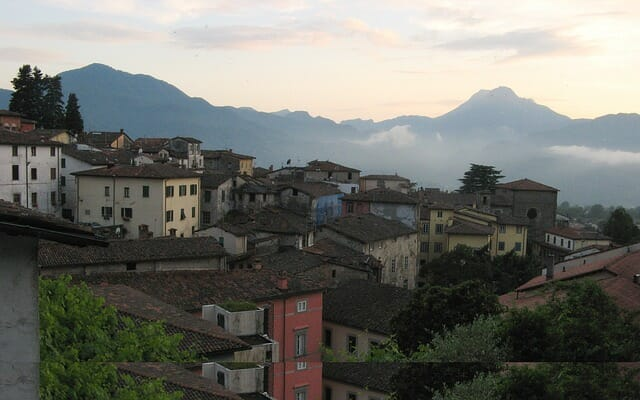 View of a tuscan town from above with mountains in the back while the sun starts to set