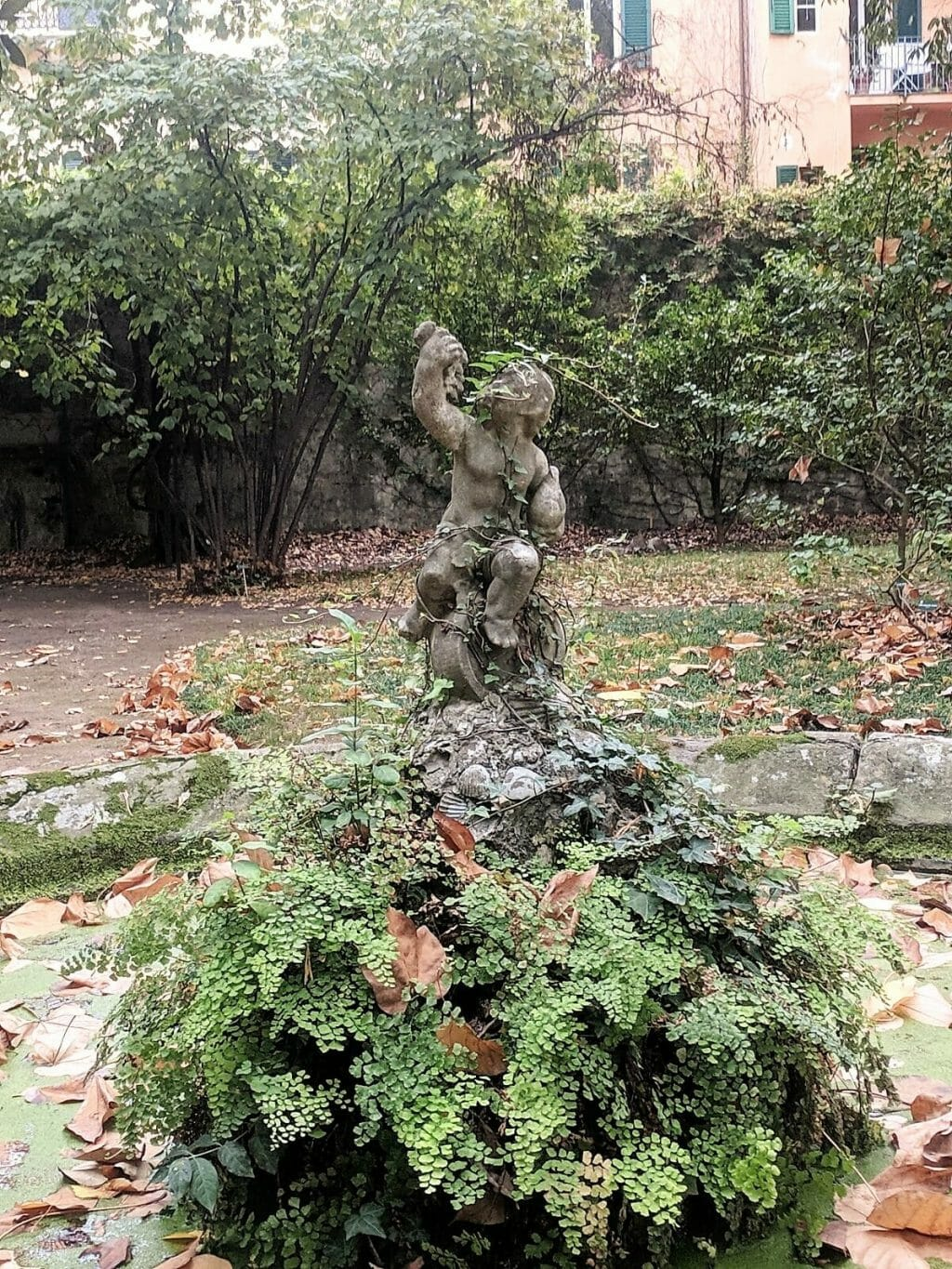 Old stone fountain covered with leaves in a picturesque Pisa garden
