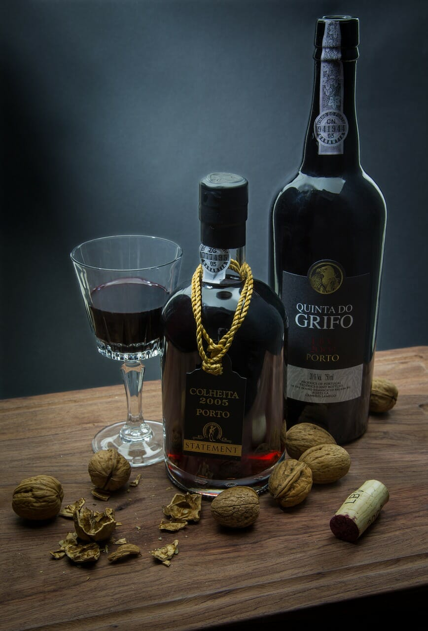 Two bottles and a glass of port wine surrounded sparsely by walnuts and a cork