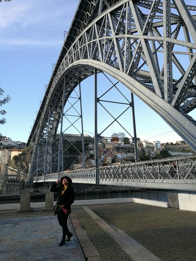 Woman standing at the very bottom of the bridge, smiling and looking up in wonder