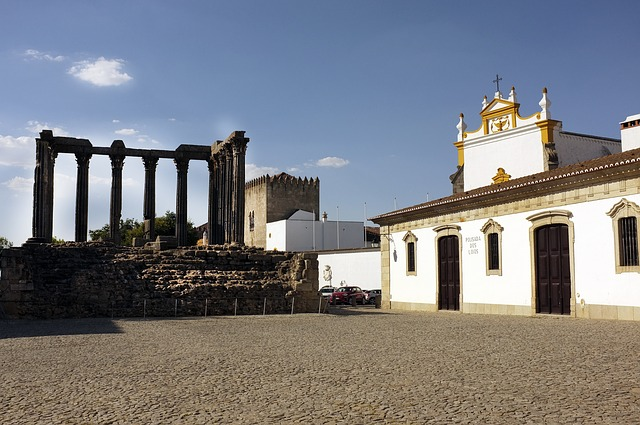 To the left is ruins of an arena while to the right is a perfectly preserved white and gold church