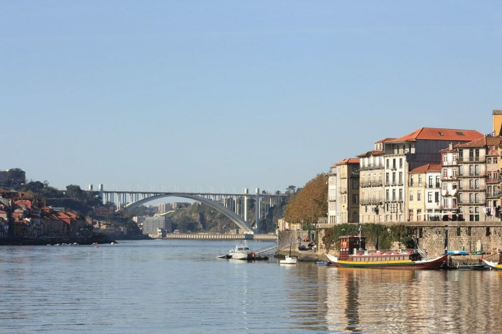 Picture from the short of the river, looking out on boats, the Dom Luis bridge, and part of the town itself