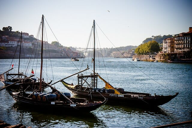 Small boats floating on the River Douro with the bridge in the distance