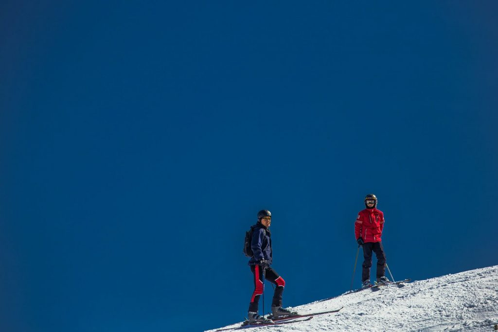 Two people making a trek up a snowy mountain in Austria