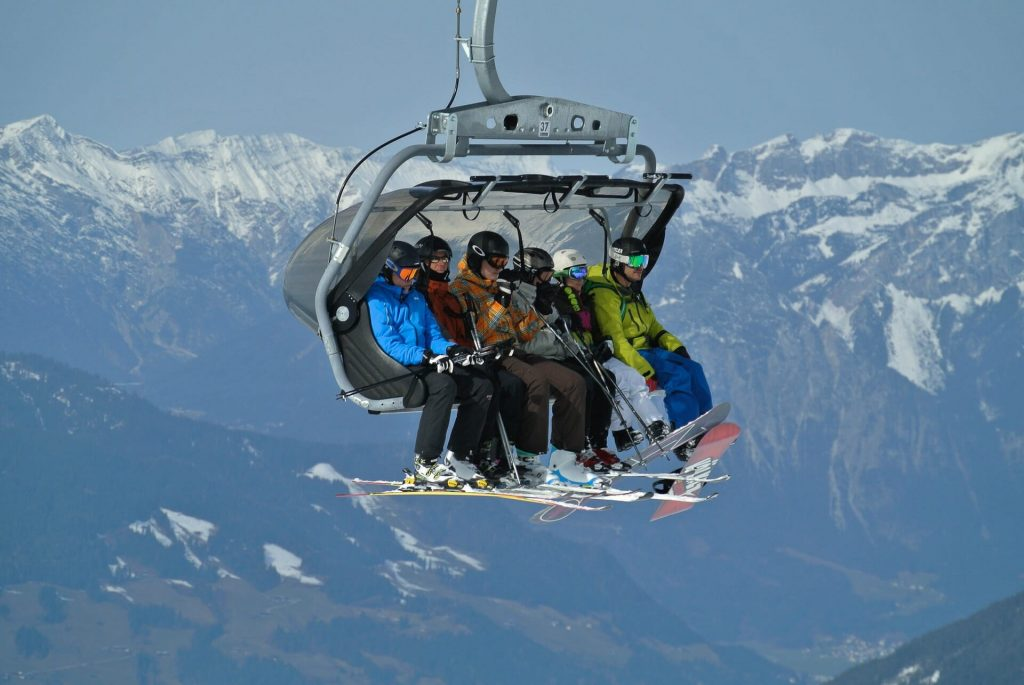 Six people packed on a ski lift, ready to get off