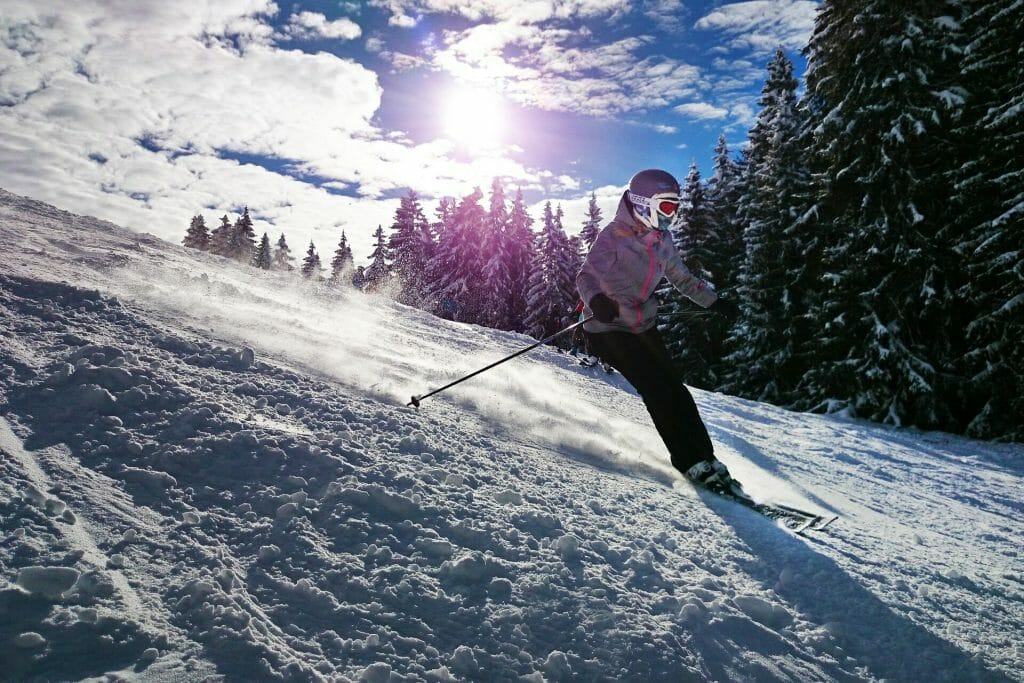 Girl skiing down slopes under the bright sun