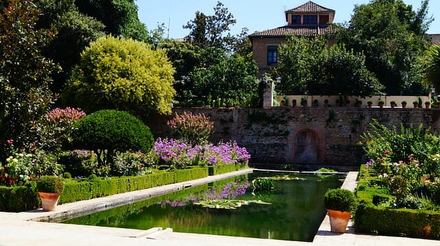Spanish gardens with lush bushes and a clear pond