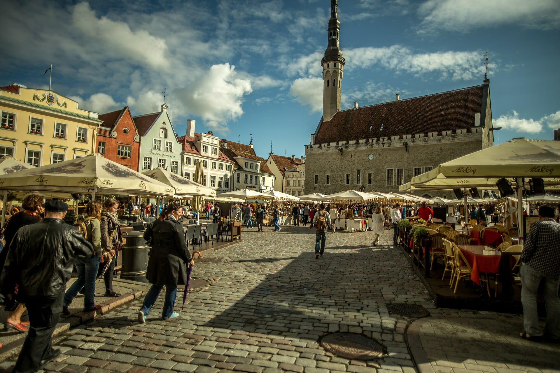 Hustle and bustle of the Tallinn town square with a church in the background