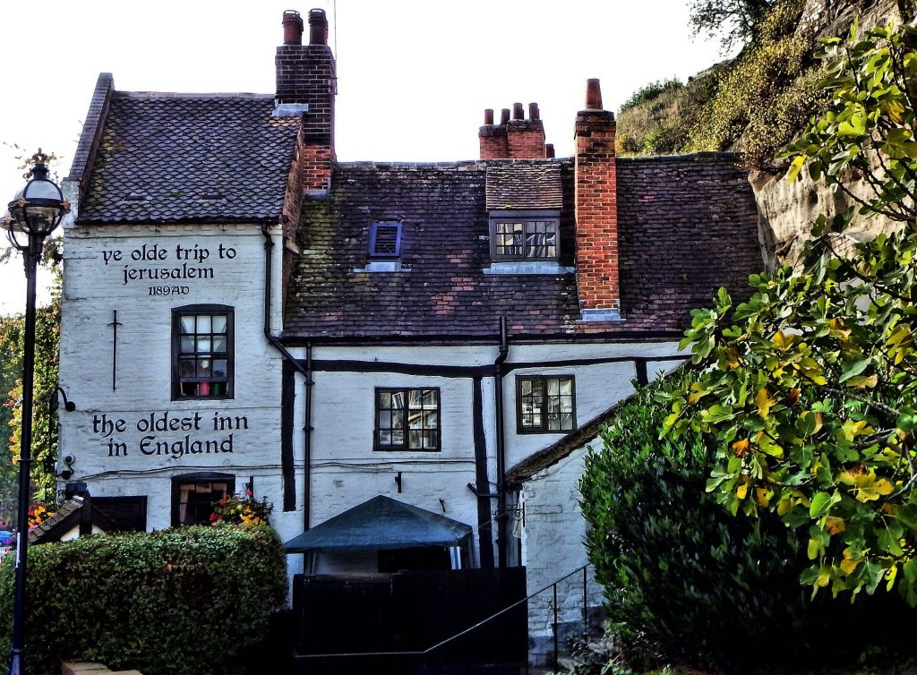 Side view of the oldest inn in England surrounded by lush trees and bushes