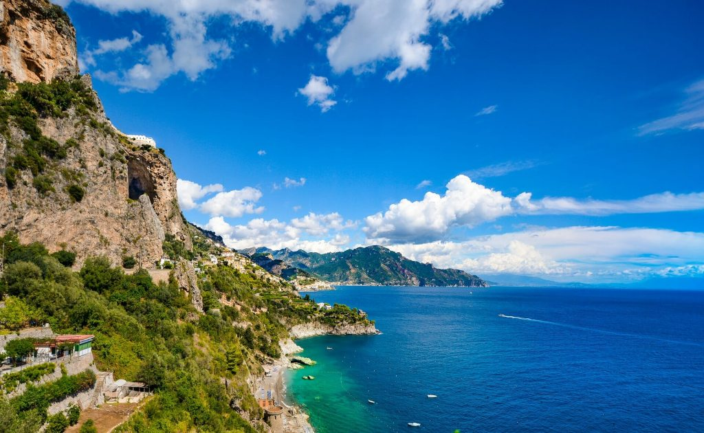 Cliffs overlooking an untamed beach by the crystal water under a clear sky