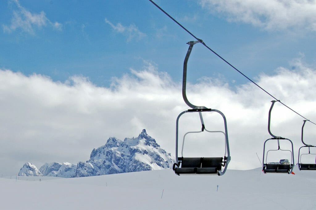 Chair lifts suspended over the snowy slopes with the imposing Dolomites in the background