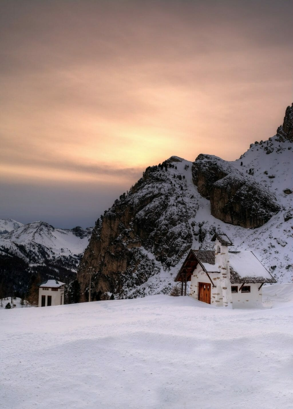 Sunset in the west side of the Arabba area, a peaceful little cottage rests covered and surrounded in snow