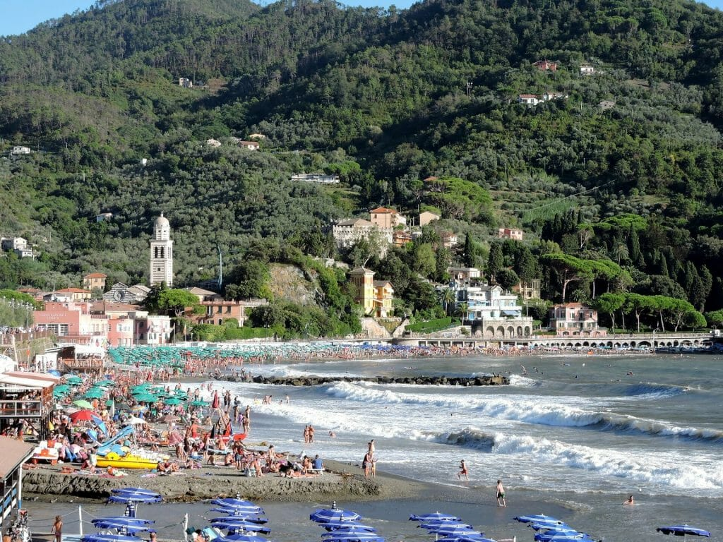 A plethora of people having a beach day on the sandy shore of Levanto