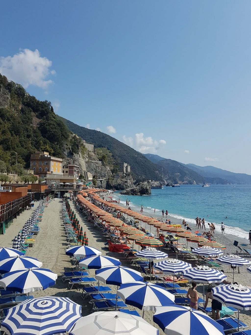 Clusters of colorful beach umbrellas shading visitors and Monterosso locals