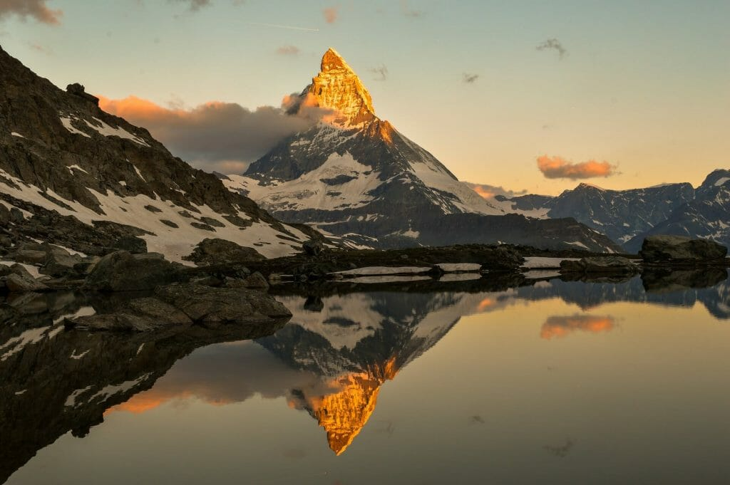 The matterhorn glowing heavenly while being perfectly reflected into the lake below