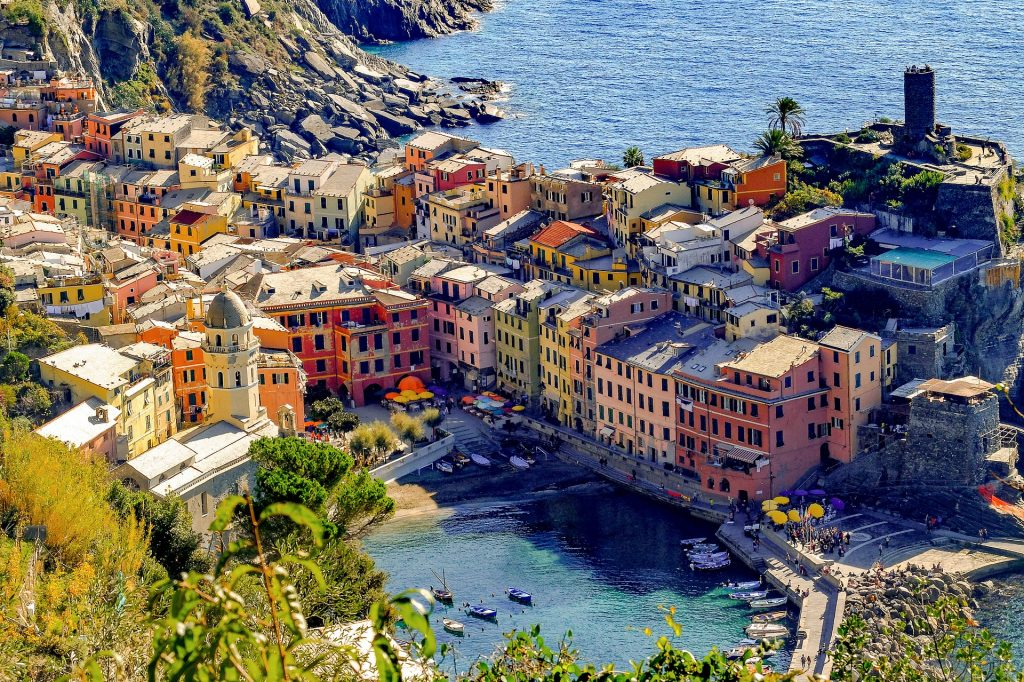 Multi-colored building lining the cliffs overlooking crystal blue Italian water
