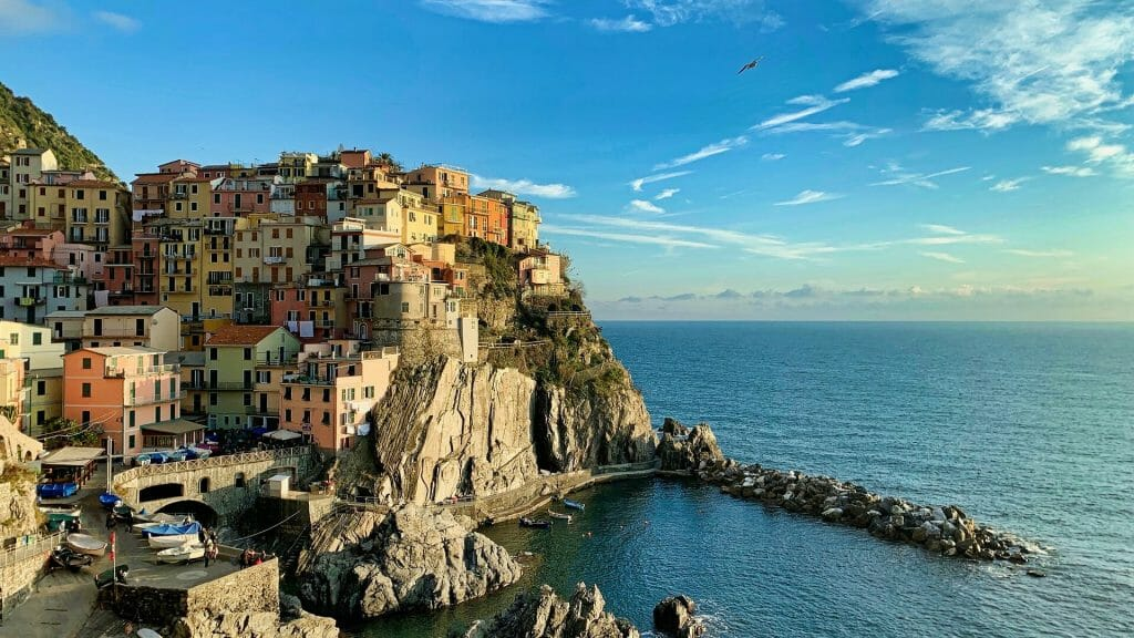 Beautiful pastel buildings surrounding the beachy cliffs over the ocean in Manarola