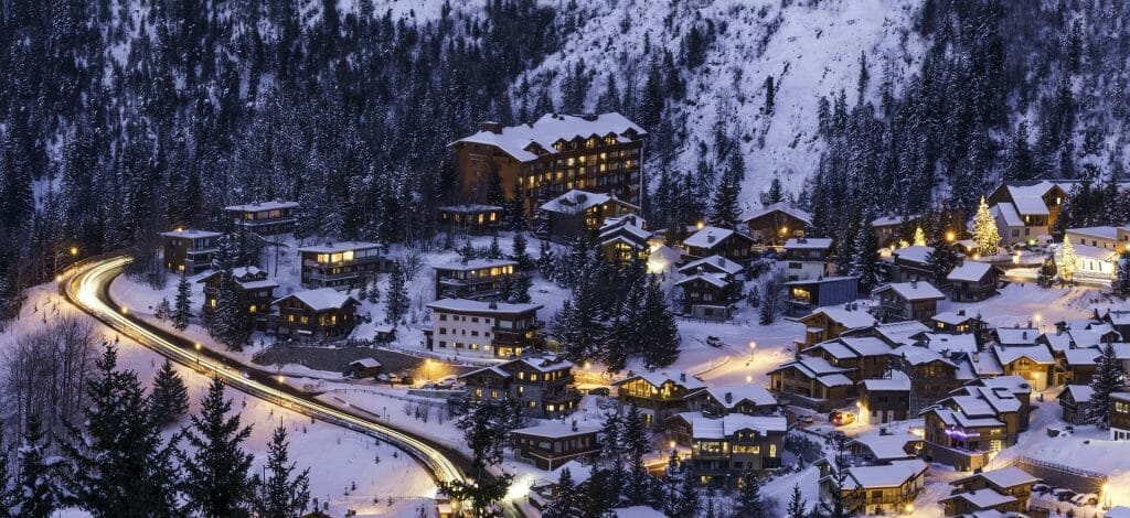 Wintery village in the mountains glowing with light and gently blanketed with snow