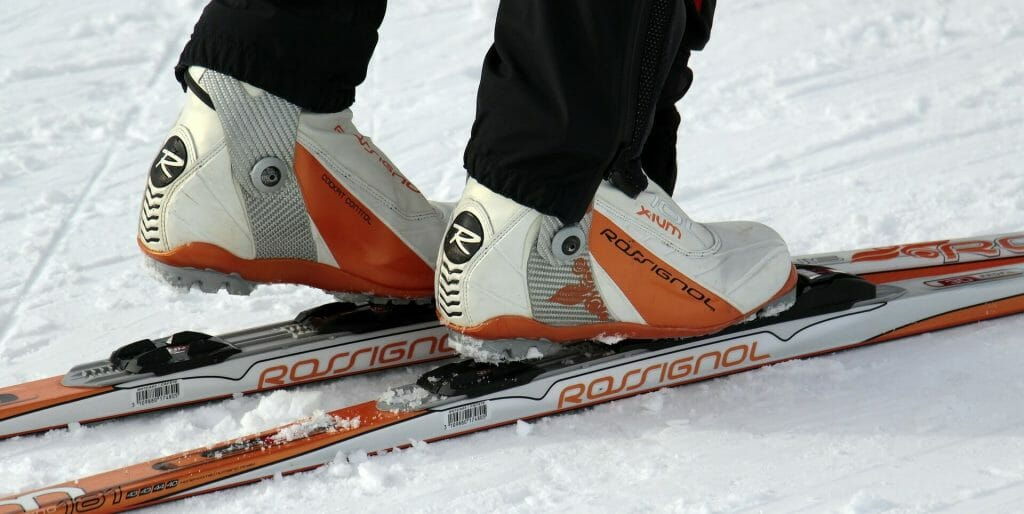 Ski boots being attached to skis on the snow floor