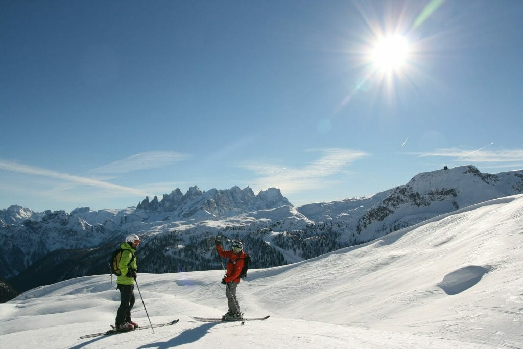Two skiers on the Dolomite slopes of Italy on a sunny day