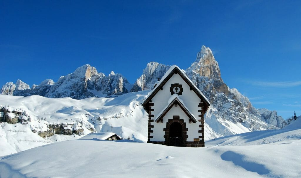 Little Italian church in the middle of the Italian alps surrounded by fallen snow