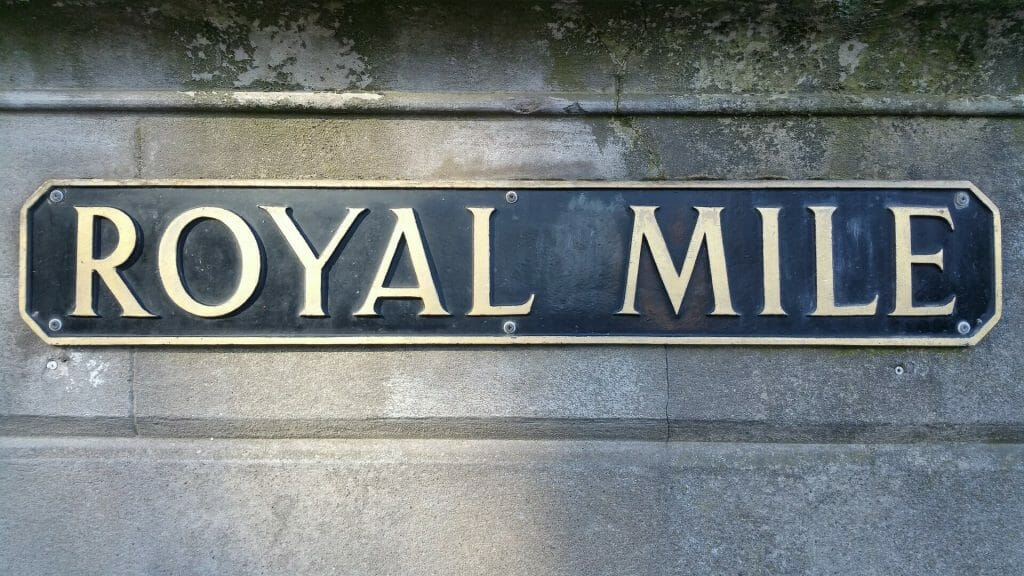 "Metal sign saying ""Royal Mile"" on a stone mount"