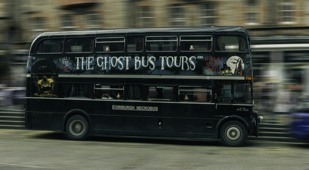 Black double decker ghost tour bus with the Edinburgh logo on the side, speeding down the street