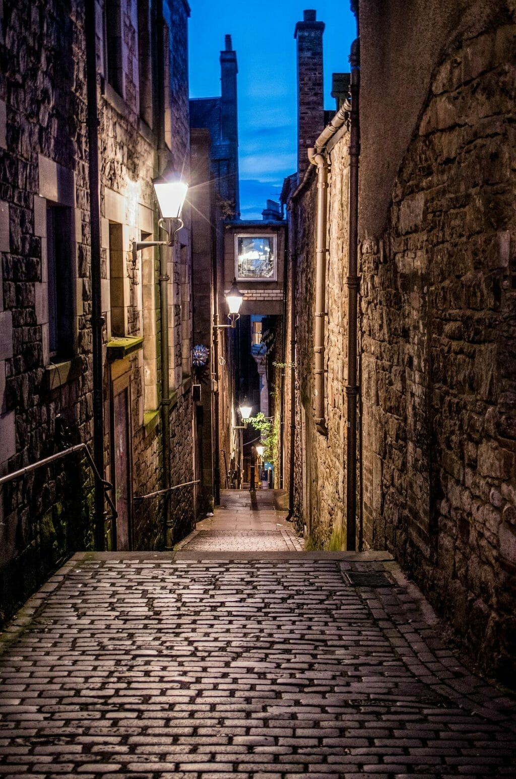 Cobblestone alley in Edinburgh in the evening with a lamp glowing with light