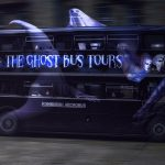 """Black tour bus with a man creatures slicking away from it; tour bus is titled """"Ghost Tour Bus"""""""