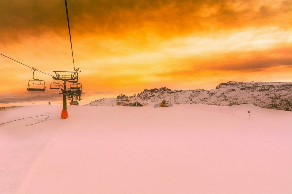 Sunsetting on the snowy Italian ski slopes, the chair lifts hanging over head