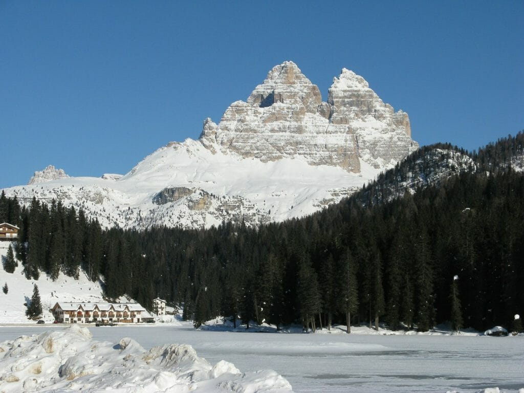 Peaks from a distance in the forest with a frozen lake and snow blanketing everything else