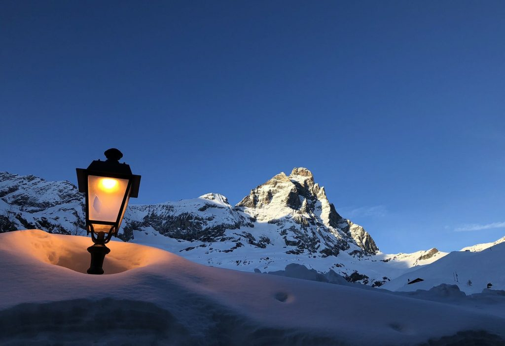 A street lamp illuminating the high snow with Mount Matterhorn in the back