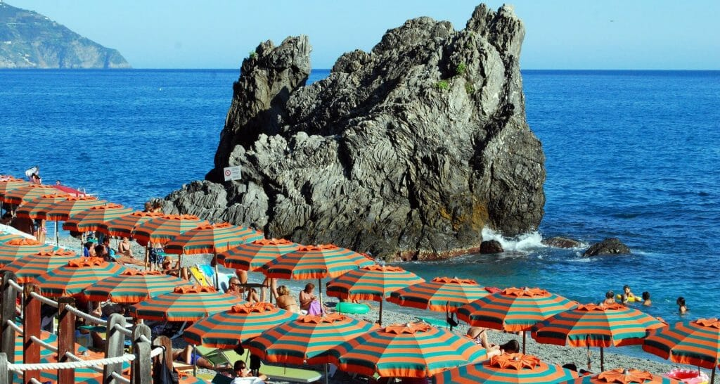 Sea boulder in the background of a sea of orange and green beach umbrellas