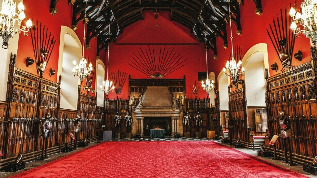 Inside Edinburgh castle, red room with brown detailing and an unlit fireplace