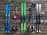 Blue and green skis laid out on the floor with their poles by their sides