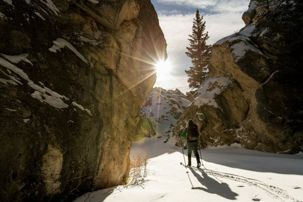 Person cross country skiing between towering cliffs