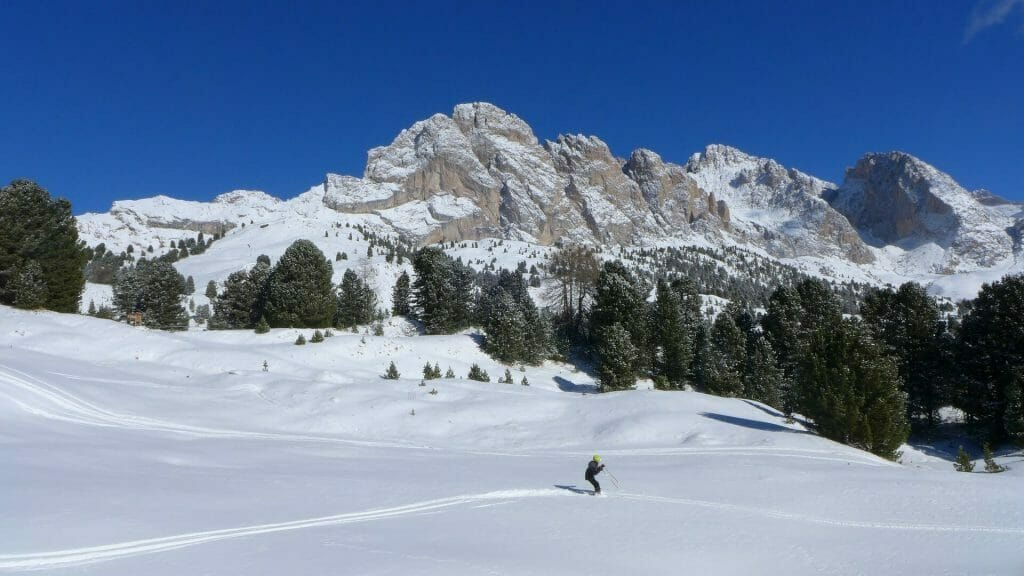Person skiing the Dolomite slopes on a sunny day with more mountains in the distance