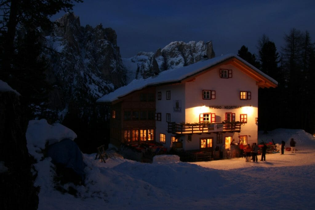 Ski cabin glowing in the winter night with people mingling around