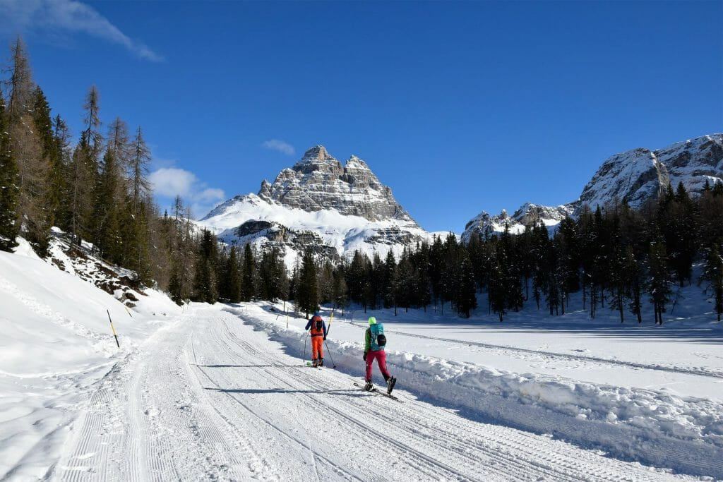 People hiking the snowy trail in Three Peaks, Italy