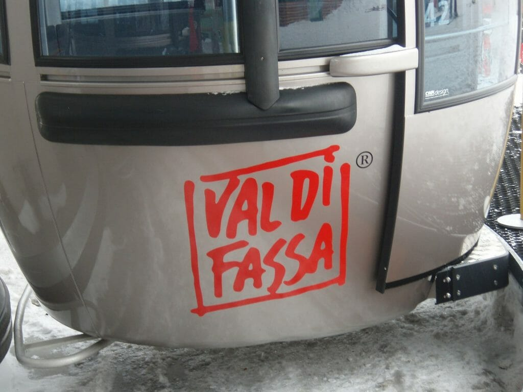 Chair lift with the words Val Di Fassa in bright red