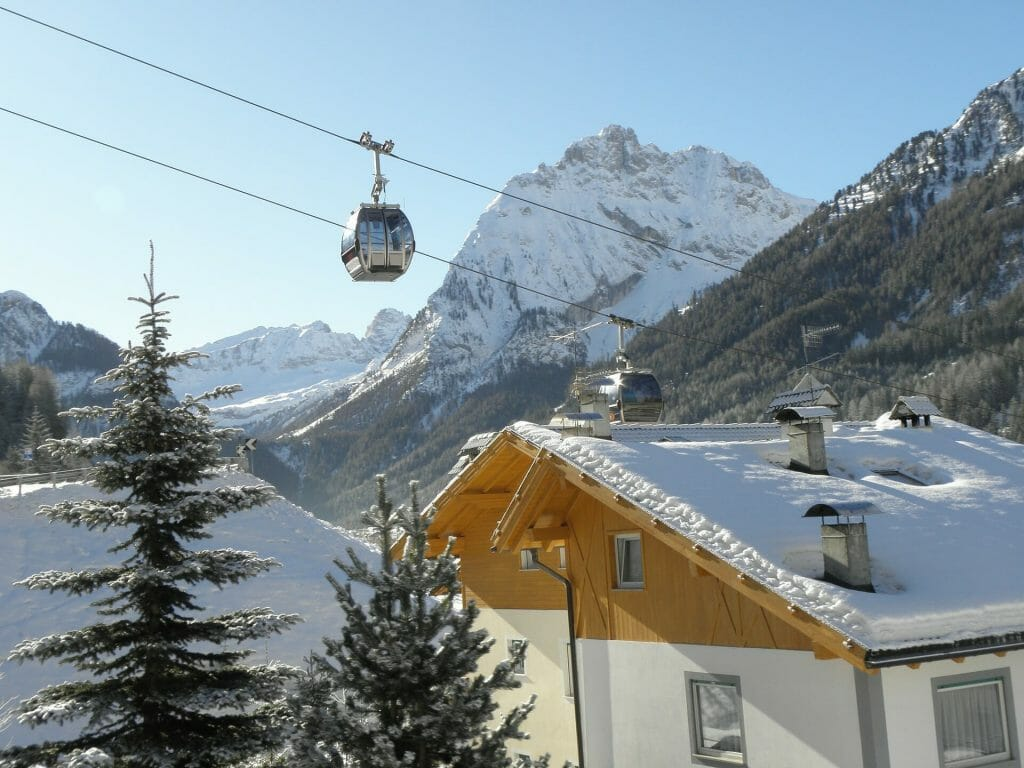 Ski lifts going over a beautiful ski chalet in Val Di Fassa Italy