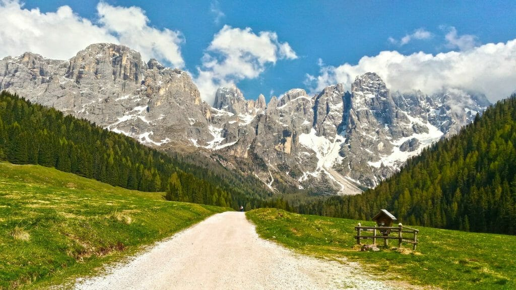 Sunny day on a trail with the snowy Dolomites in the background