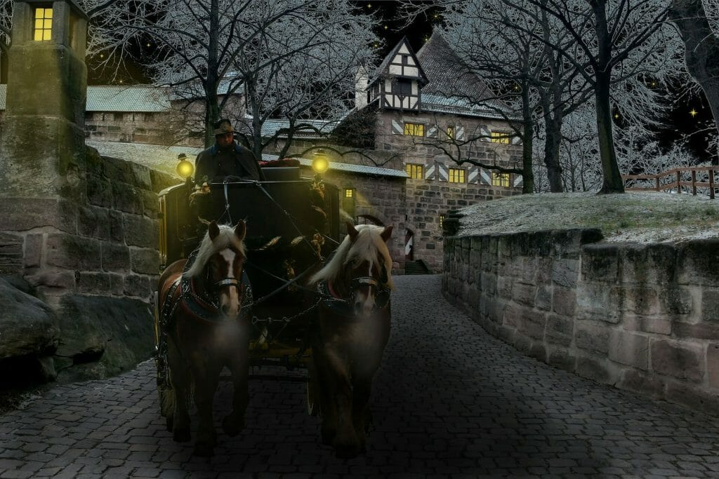 Man driving a horse drawn carriage out of an old town over a cobble stone bridge