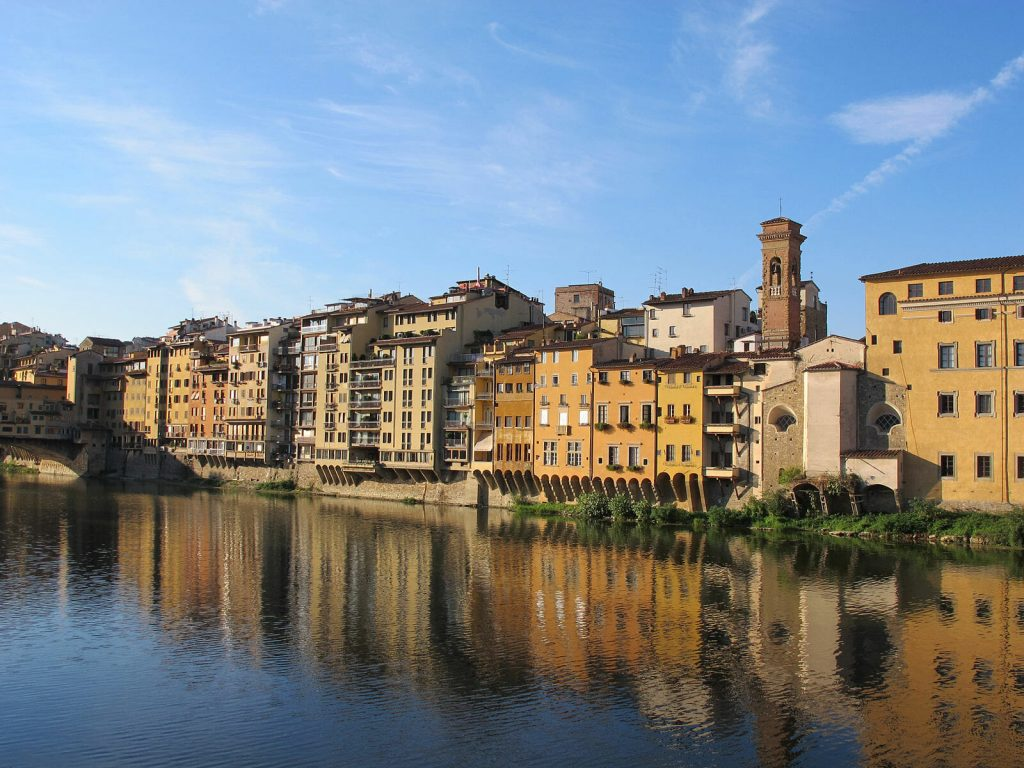 River reflecting the varying beige building back on the sunny day in Florence